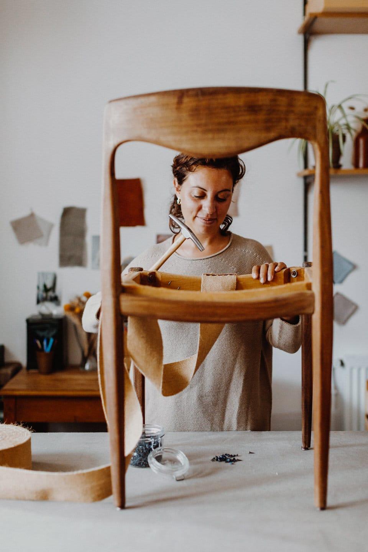 tapissiere renovant une chaise en bois