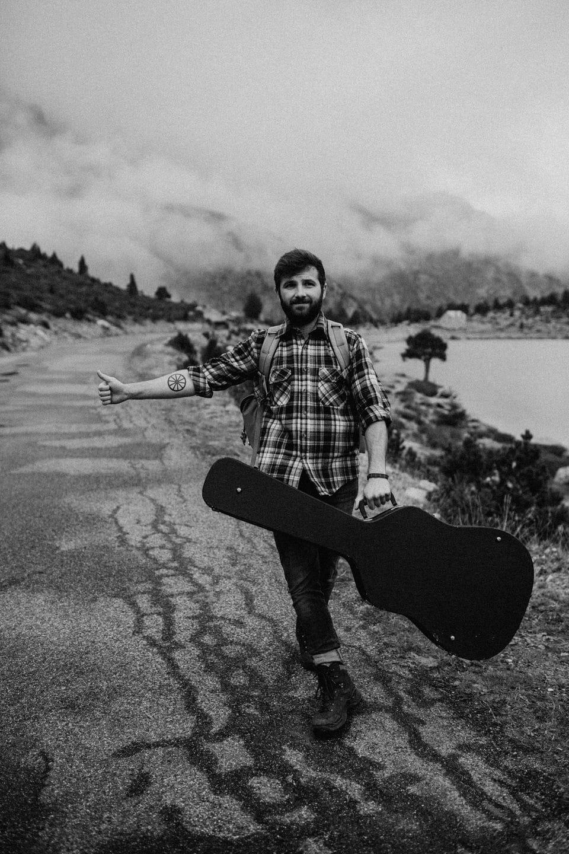 Musicien qui fait du stop sur route de montagne